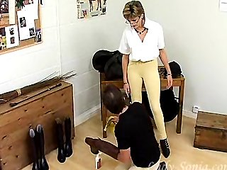 Servant licks boots for mature Mistress.