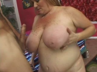 Greased blonde haired fatty stands on knees to give a crazy breastjob and dt